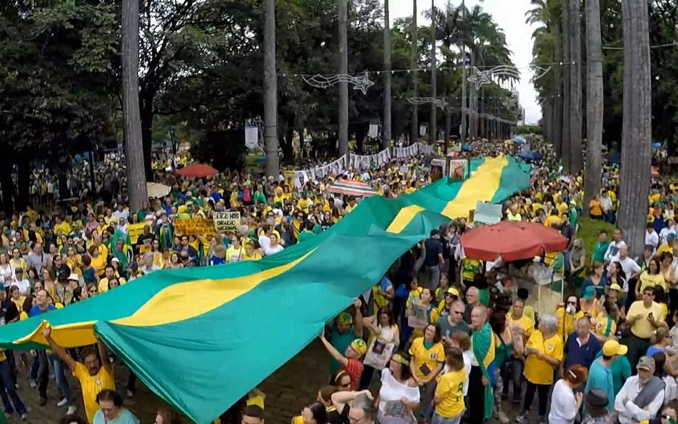 Bandeirão verde e amarelo é estendido na Praça da Liberdade, em Belo Horizonte.