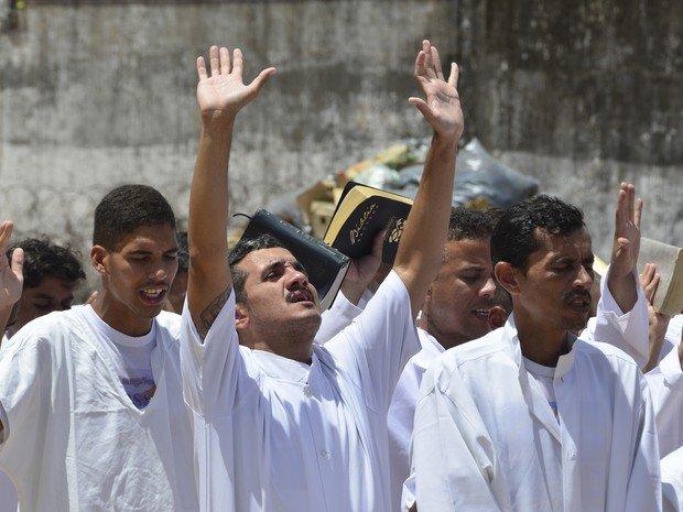 Emocionados, presos entoam louvores durante a cerimônia.